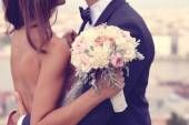 Fotografie Detail of a bride and groom embracing. Bride holding beautiful wedding bouquet