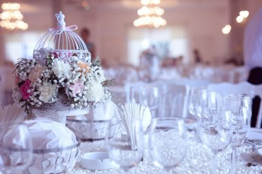 Birdcage with flowers on wedding table