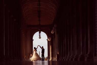 Bride and groom dancing in a tunnel