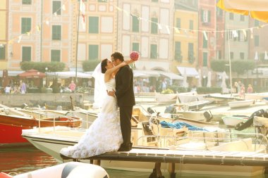 Bride and groom near port with cityscape