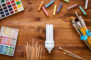 Artist brushes, paints, chalks and lamp