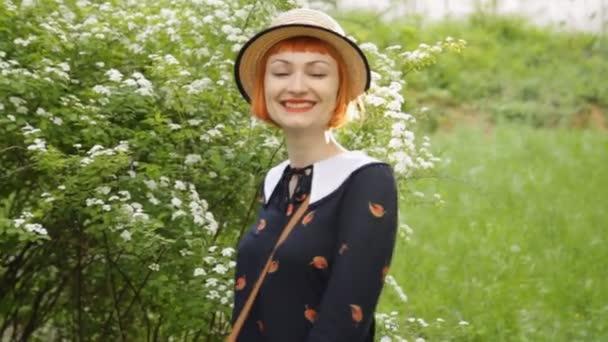 schöne rothaarige junge Frau, die tanzt, wirbelt, schwingt, lächelt, flirtet. attraktive und fröhliche Pin-up-Girl in einem Retro-Kleid und Hut. positive Emotionen. glücklich und freudig.