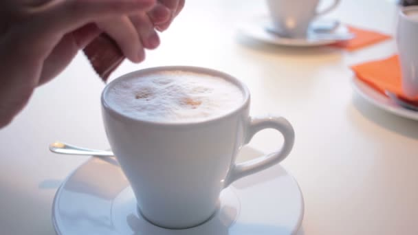 Female hand with cup of coffee in a coffee shop