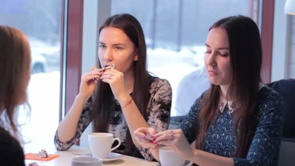 Tři kamarádky usmívající se pít kávu a komunikovat