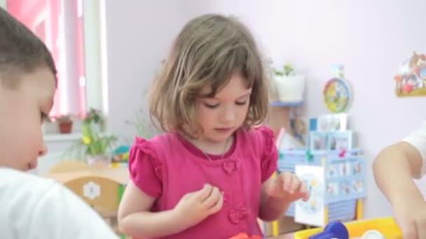 Malá holčička hraje lékaři ve školce s ostatními dětmi