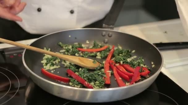 Chef prepares vegetables in a frying pan