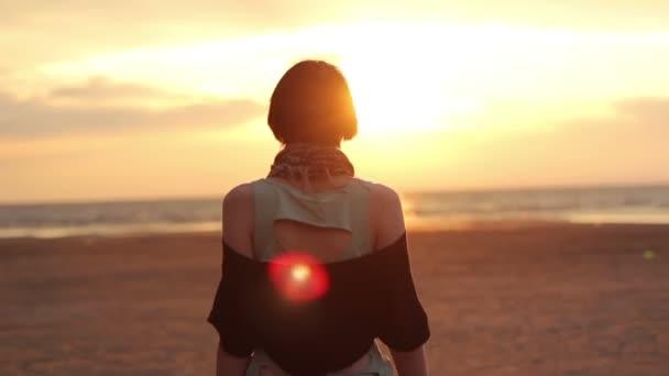 Dívka chodí na pláži při západu slunce