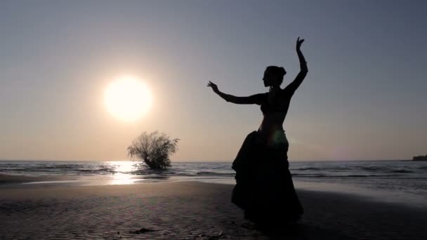Silhouette girl dancing exotic dance on beach