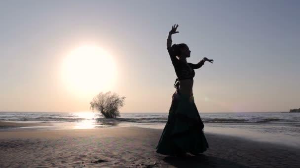 Silhouette Mädchen tanzt exotischen Tanz am Strand