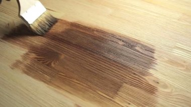 Man die gehurkt op de houten vloer verf een brede kwast in bruine