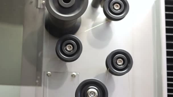 Industrial machine works in a factory. Rolling machine pulls the wire.