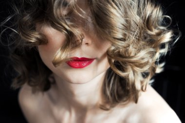 portrait of a young curly girl with dark red lips