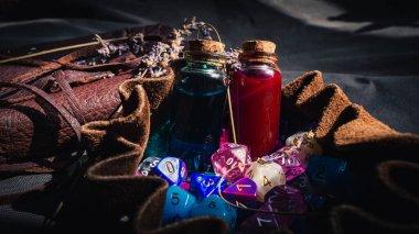 İki iksir şişesinin yakın plan görüntüsü, deri kaplı bir defter, güneş ışığında RPG zarları olan kahverengi deri bir zar torbası.