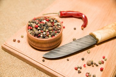 The knife, a mixture of grains of pepper on a wooden surface