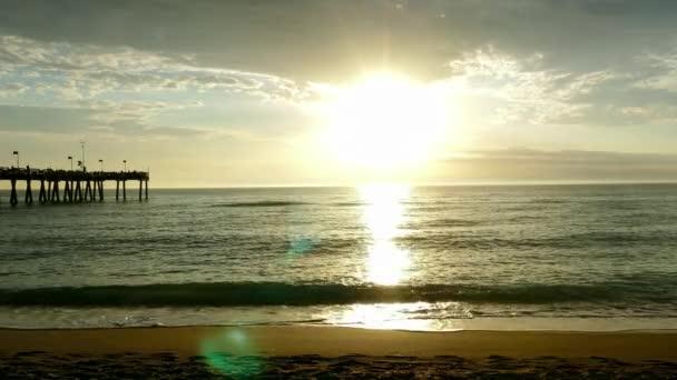 Zlaté slunce s rybářské molo v dálce