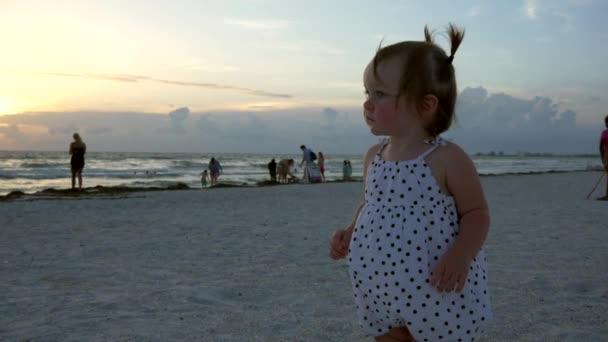 Roztomilá holčička stojí na pláži, ukázal na slunce, 4k