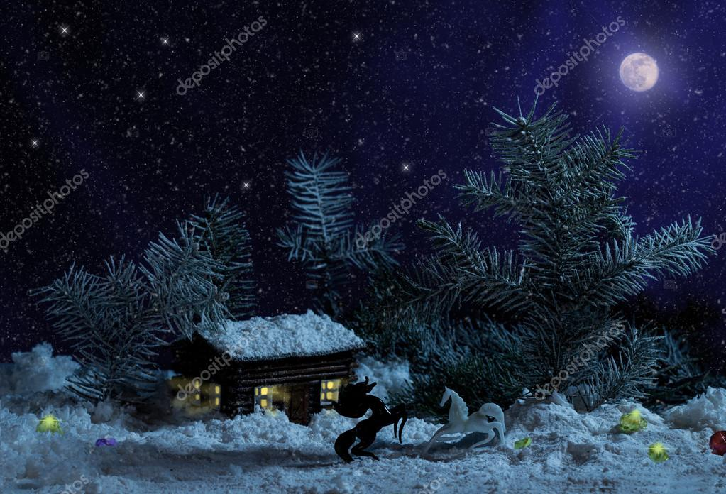 White and black horses before Decorative wood house with lights inside on black background with moon, firs and stars. Rural Christmas night scene