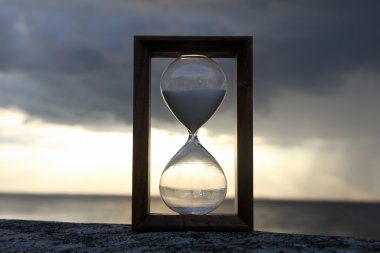 Time glass on concrete parapet over dark sky