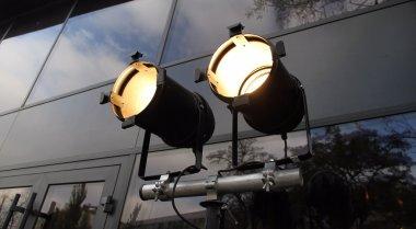 Spotlights on tripod over glass wall