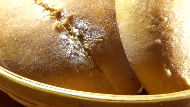 Hot baking bread. Sliced bread and slider buns in wicker breadbasket isolated