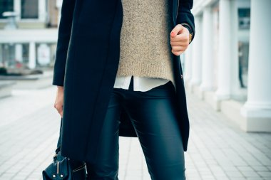 Close-up of a woman in a sweater, coat, black pants