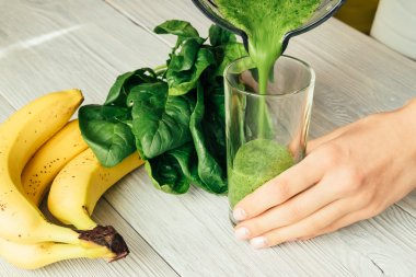 Female hands pouring green smoothies with spinach in a glass