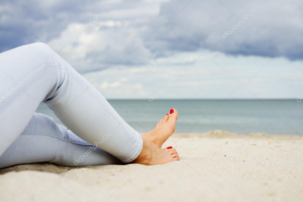 220e5de415 Γυναικεία πόδια στο τζιν πάνω στην άμμο της παραλίας — Φωτογραφία ...