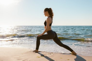 Sport girl on a beach doing lunges exercises