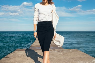Elegant woman in a skirt and cardigan walks on the background of