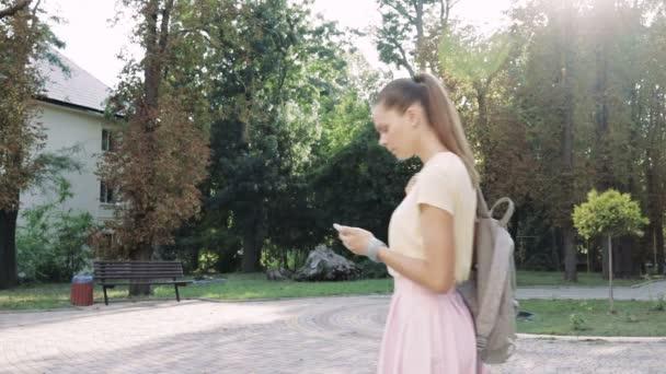 Mladá štíhlá žena v růžové sukni a žluté tričko používá navigaci na vašem smartphonu a jít ve směru