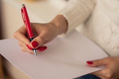 Female hand writing on a sheet of paper