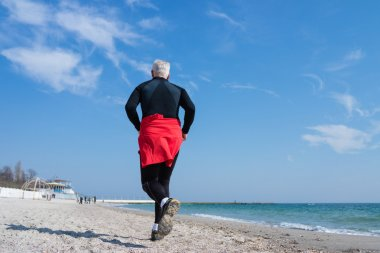 Gray-haired man running on the beach