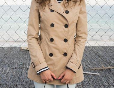 Girl in a beige coat on the coast