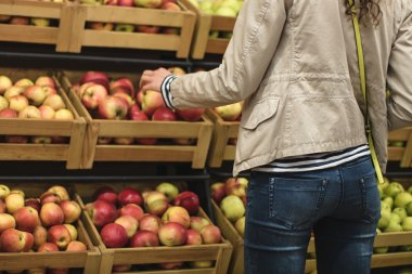 Girl in the beige jacket and blue jeans buys apples