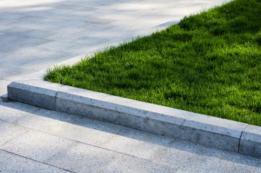 Trim the lawn in the park on the sidewalk