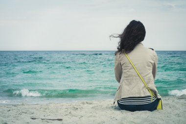Young cute girl with curly hair sitting on an empty beach