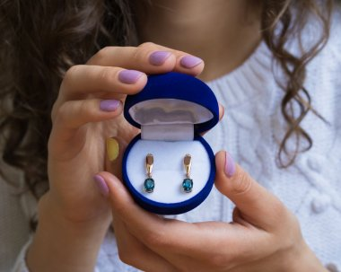 Female hands holding a box of gold earrings