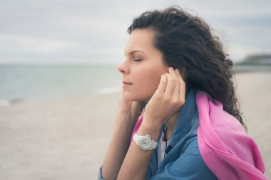 Young woman with closed eyes listening to music with headphones on the beach. She sitting on  sand and breathe the fresh sea air, she is dressed in a denim shirt on her shoulders pink cape. Soft light stock vector