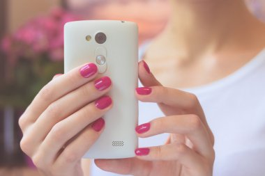 Mobile smart phone in female hands with a pink manicure on the background of pink flower and girl in a white T-shirt