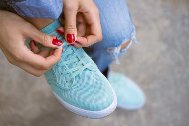 Female hands with a red manicure knotted laces on sports shoes
