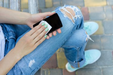 Hands of a young girl wipe mobile phone antibacterial cloth