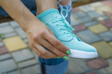 Female hand wipe cloth shoes outdoors