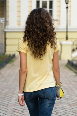 Attractive slim young woman with curly brown hair is walking on