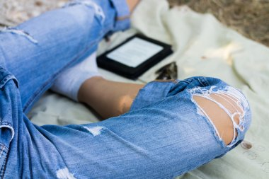 Female legs in torn jeans, electronic book and glasses on the na