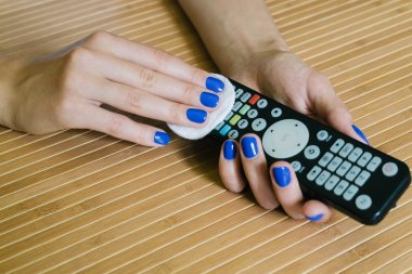 Female hands with a napkin wipe the remote control at the wooden