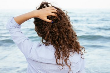 Young woman in shirt looking at the sea and keeps her hair
