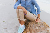 Photo Woman in beige pants and a denim shirt and turquoise sneakers si