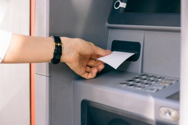 Female hand holding a receipt obtained from the ATM after withdr