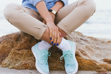 Woman in beige pants and a denim shirt and turquoise sneakers si