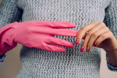 Woman in a gray sweater removes pink cleaning gloves closeup